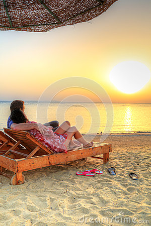Couple in hug watching together sunrise on the bea