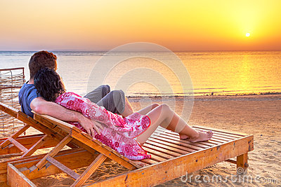 Couple in hug watching together sunrise over Red S