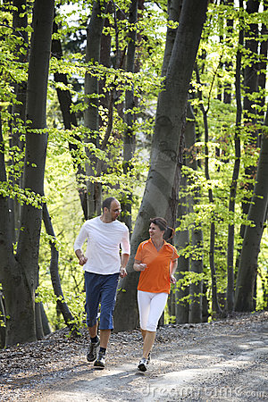 Couple jogging in beech forest