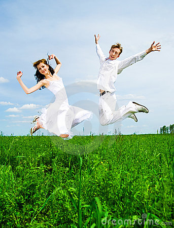 Couple jump in a meadow
