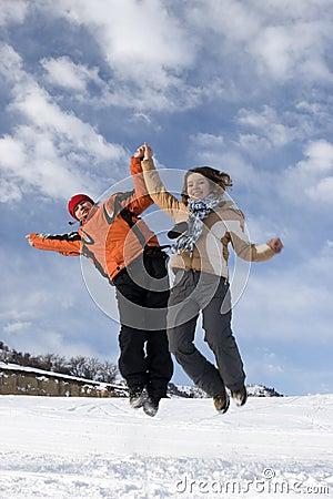 Couple jump over blue sky