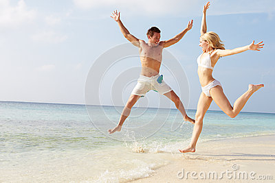 Couple Jumping In The Air On Tropical Beach