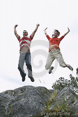 Couple Jumping With Arms Raised Over Rock