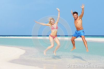 Couple Jumping On Beautiful Tropical Beach