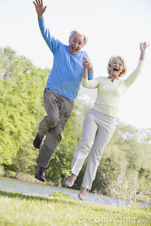 Couple jumping outdoors at park by lake smiling