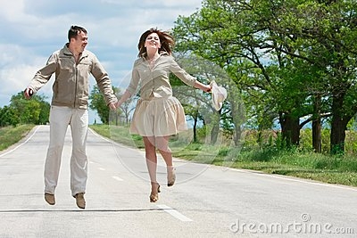 Couple jumping on rural road