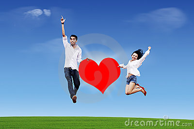 Couple jumping on the sky with heart