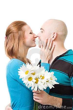 Couple kissig holding flowers