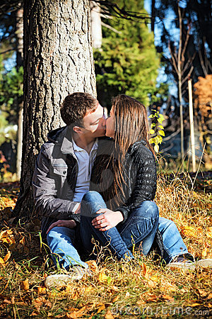 Couple kissing autumn afternoon in the park