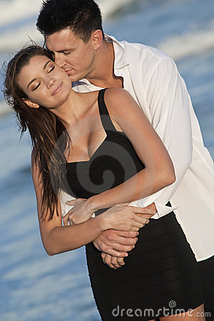 Couple Kissing In Romantic Embrace On Beach