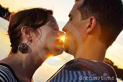 Couple is kissing at sunset