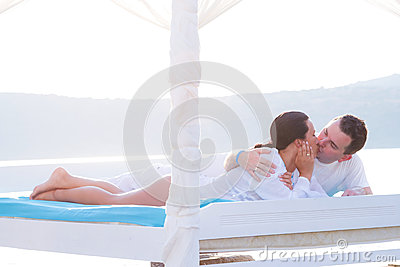 Couple kissing on white bed at the sea