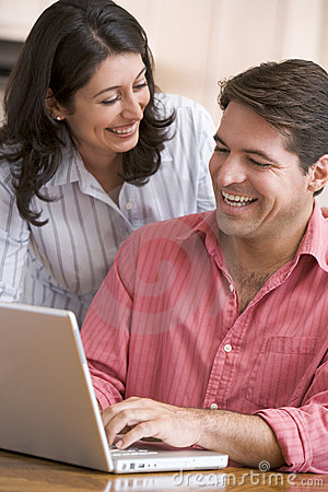 Couple in kitchen using laptop smiling