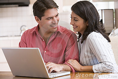 Couple in kitchen using laptop and smiling