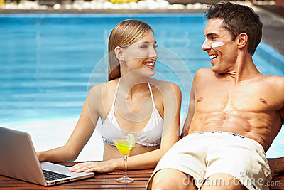 Couple with laptop at pool