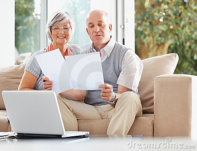 Couple with laptop reading documents