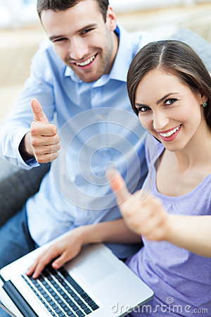 Couple with laptop showing thumbs up