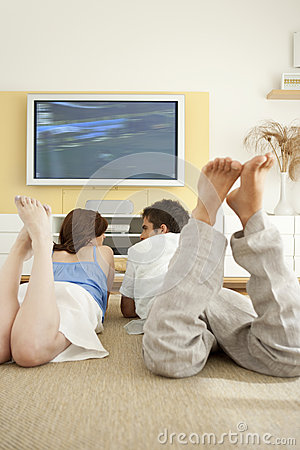 Couple Laying Down on Floor Watching TV