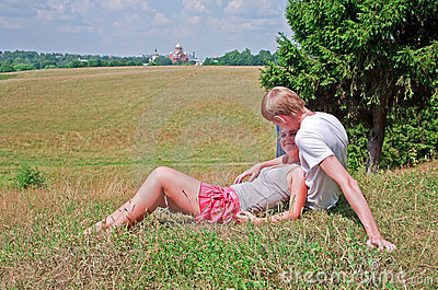 Couple laying on grass near meadow
