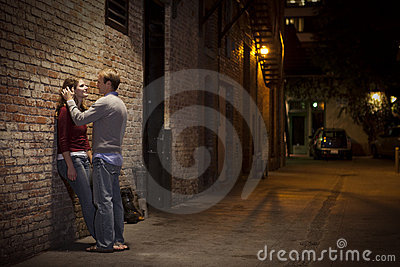 Couple leaning against brick wall in alley way