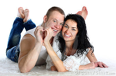Couple lie on the floor nd making heart by hands