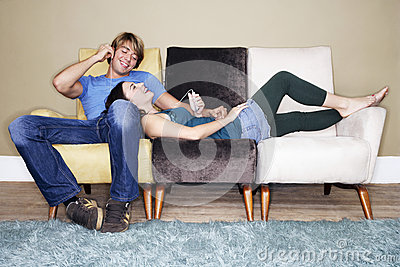 Couple Listening To MP3 Player On Sofa