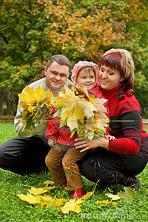 Couple and little girl collect maple leafs In park