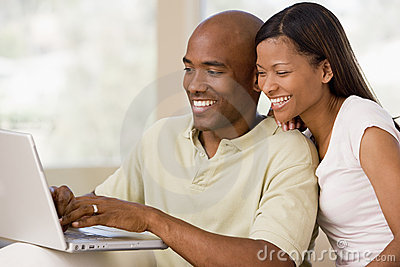 Couple in living room using laptop