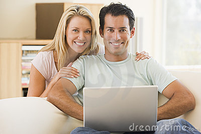 Couple in living room using laptop smiling