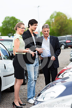 Couple looking at car on yard of dealer