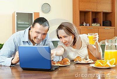 Couple looking e-mai  during breakfast