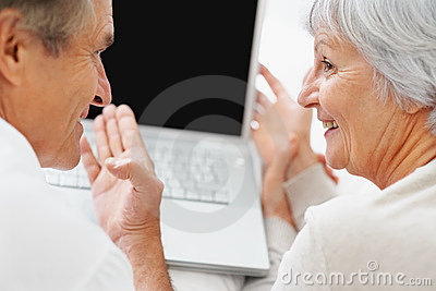 Couple looking at eachother while using a laptop