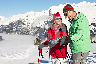 Couple Looking At Map Whilst On Ski Holiday