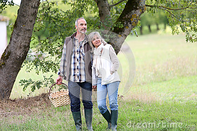 Couple looking for mushrooms in countryside