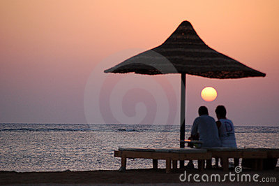 Couple looking at sunset sea