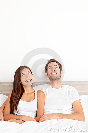 Couple looking thinking in bed