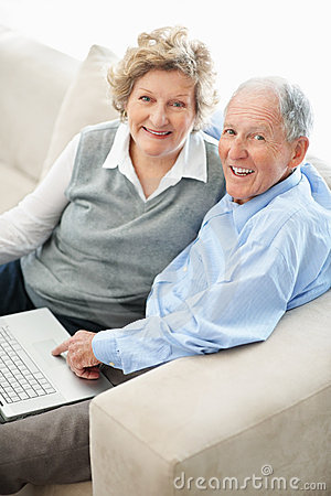 Couple looking at you while working on laptop