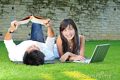 Couple In Love In The park reading and surfing