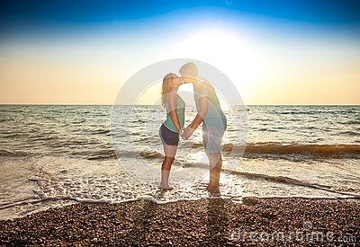 Couple in love standing in water and kissing