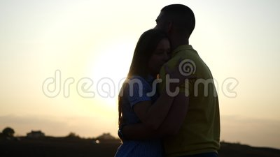 Silhouettes of a Bearded young man and his girlfriend hugging, snuggling together and kissing. Young charming couple. A couple in love in the sunset light. Young stock video footage