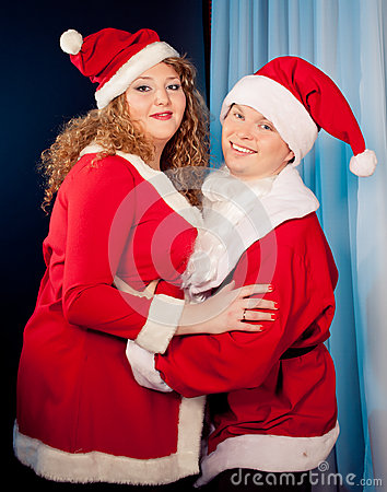 In love wearing santa hats near christmas tree fat woman and slim fit