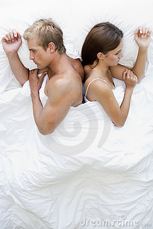 Couple lying in bed back to back looking unhappy