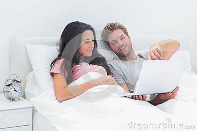 Couple lying in bed looking at a laptop