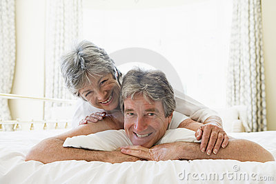 Couple lying on bed together smiling