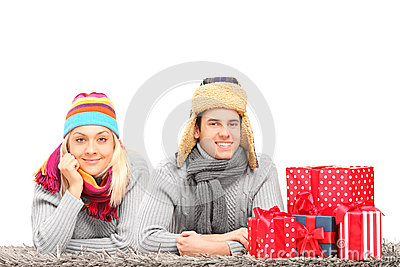 Couple lying on a carpet near presents