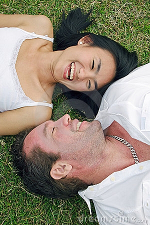 Couple lying on lawn and laugh