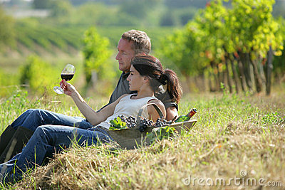 Couple lying in a vineyard tasting wine