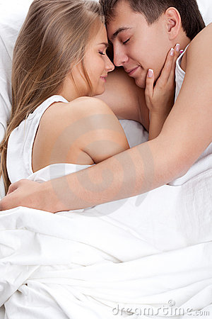 Couple lying on white bed