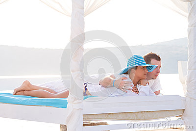 Couple lying on white bed at the sea