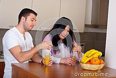 Couple make fresh orange juice